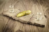 stock photo of vodka  - Pickled cucumber and vodka on old wooden table - JPG