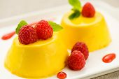 picture of custard  - Baked custard dessert with ripe red raspberries and fresh mint close up view on a plate - JPG