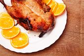 image of roast duck  - Roast duck with oranges on wooden background - JPG