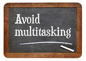 picture of multitasking  - Avoid multitasking advice  on a vintage slate blackboard - JPG