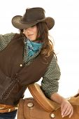 foto of cowgirls  - a cowgirl leaning on a saddle with a smile on her face - JPG