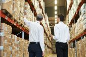 stock photo of dispatch  - two managers workers in warehouse with bar code scanner - JPG