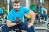image of triceps brachii  - fitness man at biceps brachii muscles exercises with training dumbbells in gym - JPG