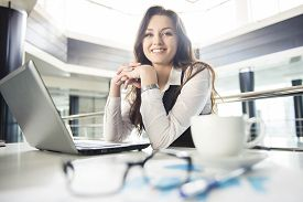 image of mature adult  - Smiling young business woman working for a laptop in a modern office - JPG