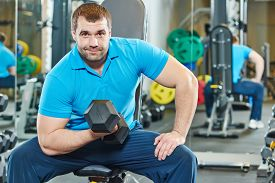 foto of triceps brachii  - fitness man at biceps brachii muscles exercises with training dumbbells in gym - JPG