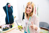 stock photo of tailoring  - Smiling female tailor standing in workshop and showing thumb up - JPG