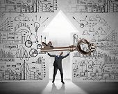 picture of keyhole  - Young businessman and keyhole at background lifting big key above head - JPG