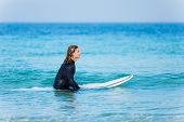stock photo of board-walk  - A young surfer with his board on the beach - JPG
