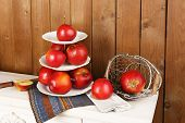 foto of serving tray  - Tasty ripe apples on serving tray on wooden background - JPG