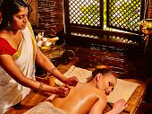 image of panchakarma  - Young woman lying on stomach having oil Ayurveda spa treatment - JPG