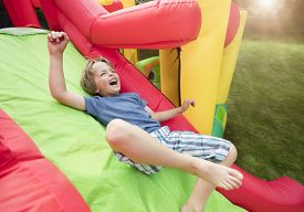 picture of inflatable slide  - Boy jumping down the slide on an inflatable bouncy castle - JPG