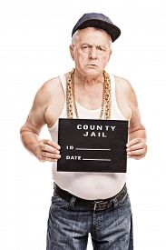 stock photo of mug shot  - Vertical shot of a senior gangster in a hip hop outfit posing for a mug shot isolated on white background  - JPG