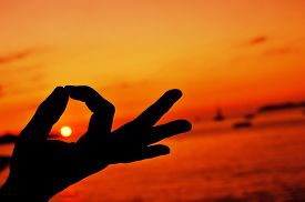 picture of mudra  - closeup of a young man meditating with his hands in gyan mudra at sunset - JPG