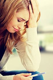 image of pregnancy test  - Sad young woman holding pregnancy test - JPG