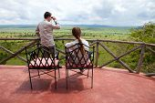 Safari vacation. Young couple in safari clothes observing beautiful national park of Tarangire in Ta
