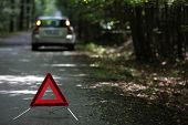 broken down car with warning triangle behind it waiting for assistance to arrive (shallow depth of f