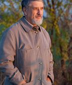 foto of older men  - Portrait of a handsome senior man standing outdoors in warm evening light - JPG