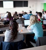 stock photo of students classroom  - young pretty female college student sitting in a classroom full of students during class - JPG