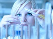 pic of retort  - Closeup of a female researcher holding up a test tube and a retort and carrying out experiments  - JPG