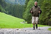 active handsome senior man nordic walking outdoors on a forest path, enjoying his retirement (shallow DOF)