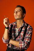 Celebrity resemblance. Johnny Deep lookalike. Stylish young man with cigarette wearing checkered shi