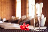 Two Glasses Of Champagne With Red Flower In A Spa Lounge. Spa Time Concept. Spa Lounge Area. poster