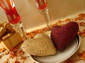 golden and red hearts, gift box and glasses on celebratory table
