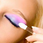 close-up da bela jovem fazer seu make-up com escova