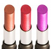 three colored lipsticks on white background