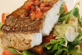 picture of plate fish food  - Barramundi dinner served on bed of vegetables - JPG