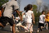 foto of school child  - Group of elementary children running through school parking lot away from viewer - JPG