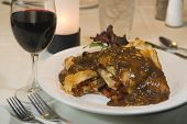 Gravy smothered stuffed chicken breast dinner and red wine