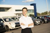 Young Woman Car Rental In Front Of Garage With Cars On The Background poster