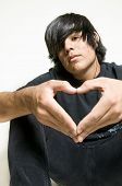 stock photo of emo-boy  - Teenage boy making heart symbol with hands - JPG