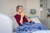 Relaxed mature woman enjoying tea sitting with blanket on a comfortable couch. Senior woman holding  poster