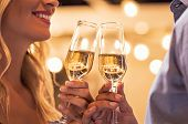 Man and woman toasting champagne flutes under light bulb outdoor. Closeup of boyfriend and girlfrien poster
