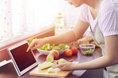 Asian Woman Use Finger Slide On Tablet Screen Prepare Ingredients For Cooking Follow Cooking Online  poster