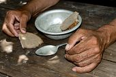 Hands The Poor Old Mans, Piece Of Bread And Empty Bowl On Wood Background. The Concept Of Hunger Or poster