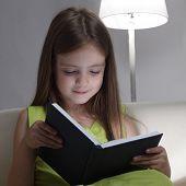 menina de beleza, ler livro no sofá