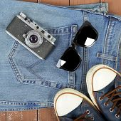 Clothes, Shoes And Accessories - Top View Retro Camera, Black Sunglasses, Gumshoes And Blue Jeans On poster