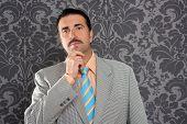 mustache retro salesman with vintage suit and pensive gesture in wallpaper