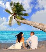 stock photo of couple sitting beach  - couple in love sitting in blue beach on vacation travel  - JPG