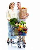 Senior couple with a grocery shopping cart. Isolated on white background.