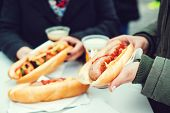 Women Eating Sausage At Street Food Festival. Czech Market In Prague. Street Food At Winter Time In poster