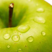 Grüner Apfel mit Wassertropfen auf seiner Oberfläche