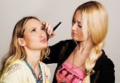 Professional visagiste applying makeup to a model