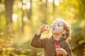 Portrait Of Funny Lovely Little Girl Blowing Soap Bubbles.cute Blonde Blue-eyed Girl In Yellow Knitt poster