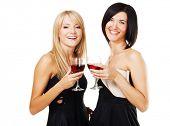 Dos bonitas a mujeres alegres con vasos de vino, blanco bzckground