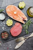 Raw Tuna And Salmon Steak And Ingredients For Cooking On A Dark Background. Top View poster