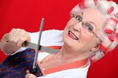 grandmother with haircurlers sharpening knives against red background